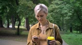perfurante : Young blonde woman with short haircut walking in park and typing on phone, holding coffee Vídeos