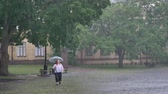 tempestuoso : Fat ginger girl is running in park under rain, holding umbrella