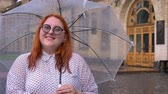 komor : Fat ginger girl with glasses is standing in rainy weather, holding umbrella, watching at camera, smiling, building on background