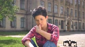 concentrando : Occupied young woman sitting and thinking then smiling at camera, happy and cheerful, park near university background Stock Footage