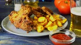 Crispy fried chicken wings with fried wedges on a plate. Breaded crispy chicken with baked potatoes for tasty dinner 動画素材