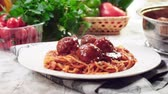 Serving spaghetti with meatballs in tomato sauce. Slow motion