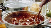 Cooking meatballs in tomato sauce to prepare spaghetti with meatballs. Slow motion