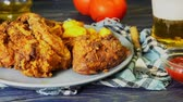 gevrek : Crispy fried chicken wings with fried wedges on a plate. Breaded crispy chicken with baked potatoes for tasty dinner Stok Video