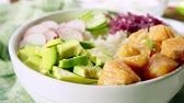 Poke bowl, traditional Hawaiian raw fish salad with rice, avocado, cucumber and radish Stock Footage