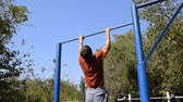 testépítő : man pulls himself up on the bar. Playing sports in the fresh air. Homemade Horizontal bar in the backyard Stock mozgókép