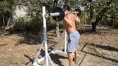 halter : man takes a bar to perform squats. Exercises in bodybuilding. sport in the backyard