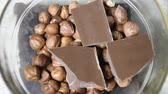 indulgência : Milk chocolate and hazelnut in a glass cup. Chopped chocolate bars and hazelnuts. Stock Footage