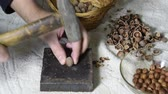 ореховая скорлупа : Chipping the hazelnuts with a hammer on the table. Smoothing of hazelnut on a slaty substrate.