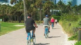 wydmy : Miami Beach, Florida - February 22, 2018: Super high definition video of visitors enjoying a bike ride along the promenade in South Pointe Park in popular South Beach.