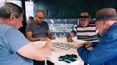 domínio : Miami, Florida USA - January 19, 2019: High definition video of elderly individuals playing the popular domino game at the historic Domino Park in Little Havana.