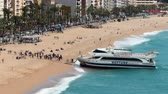 âncora : Aerial view of LLoret de Mar, When a tourist boat arrives at the beach.Hyper lapse. Village of the province of Girona (Catalonia), a springtime sunny day with the fast movement of waves and activity of people.Smooth camera movement: Zoom in.Long exposur