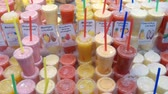 tentador : Great variety of fruit juices in glasses. Market stall of La Boqueria in Barcelona. Camera movement tracking shot left. Stock Footage