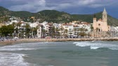 уборная : Wide view of SITGES from the sea.Time lapse. Village of the province of Barcelona (Catalonia), a springtime sunny day with the fast movement of clouds and waves.