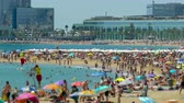 уборная : Activity on the beaches of the city of Barcelona with modern buildings background, a sunny summer day.Time lapse.Tilt-shift effect.4k.