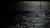 Moonlight reflection on the sea surface with water movement and light buoy the top right of the scene. Stock Footage