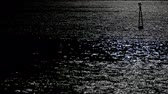 Reflection of moonlight with a light buoy and a boat passing on the top right of the scene. Stock Footage