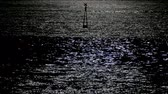 Moonlight reflection on the sea surface with water movement and light buoy the top center of the scene.