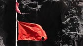 sinal de alerta : Close-up of broken red flag moving by the wind, with a background of rocks, transmitting sense of danger. Slow motion. Stock Footage