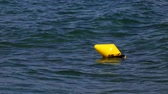 Old yellow buoy floating in the sea with the smooth movement of the waves.