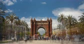 Touristic Barcelona, Arc de Triumph. Time Lapse. Long exposure. Silk effect. Panoramic view of Arch of Triumph with crowd of unrecognizable people (semitransparent) walking on sunny day.