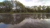 comprometido : man runs through puddles in the park. Feet closeup. slow motion Stock Footage