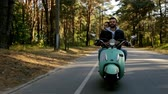 momentka : Happy couple riding a scooter in the forest. Sunny beautiful day. Dostupné videozáznamy