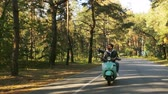 lambreta : Happy couple riding a scooter in the forest. Sunny beautiful day. Vídeos