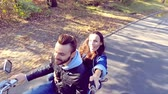 momentka : Happy couple riding a scooter in the forest. Sunny beautiful day. Selfie-stick camera view. Slow motion.