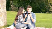 outing : Happy couple is enjoying on the green lawn. The guy and the girl are drinking wine at a picnic. Stock Footage