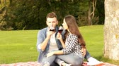 Happy couple is enjoying on the green lawn. The guy and the girl are drinking wine at a picnic. Stock Footage