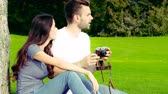 outing : Happy couple taking pictures with an old camera on a green lawn.