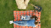 plaid : Happy couple lying under a tree and listening to music. Top view.