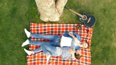 genre : A happy couple lies on the lawn and enjoys romance. Top view. Stock Footage