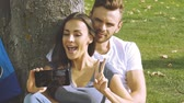 Happy couple taking a picture of themselves with a smartphone on a green lawn. Slow motion. Stock Footage