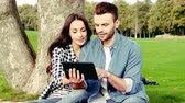 genre : Happy couple listening music or watching video in the park.