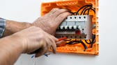 disjuntor : Video of the electrician technician who inserts and blocks the cable in the electrical panel. Construction industry. Vídeos