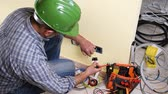 Electrician technician worker with screwdriver fixing electric cable to socket terminal in a residential electrical system. Construction industry. Building. Footage.