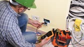 instalador : Electrician technician worker with multimeter it measures electrical voltage in a residential system. Construction industry. Building. Footage. Archivo de Video