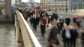 jednotnost : Time lapse of London Bridge during the morning rush hour showing endless hoards of commuters rushing to work in the city. Buses and other vehicles whizz past in the background. The river Thames can be seen flowing under the bridge. Dostupné videozáznamy