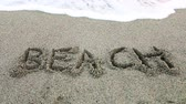 вывеска : the word beach written on the sand Стоковые видеозаписи