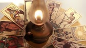 psychic : old tarot cards rotating and oil lamp