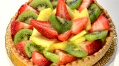 tarte : Fruit tart on red plate rotating. Pineapple, kiwi and strawberries. Stock Footage