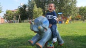 por que : child on a rocking animal cries because he wants the pacifier
