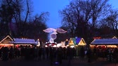 Timelapse. Blur Background With Bokeh Of Christmas Light In Europe Ukrainian Christmas Market, Xmas And New Year Winter Festival. Young Kids Happy Enjoy Smile Snow, Tree, Toy, Shop, Food, Candy In Fair In Holiday