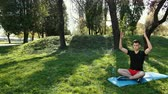 loto : Young Man In Lotus Position Sitting On Green Grass In Park. Concept Of Calm And Meditation. Hands In Shape Of Pyramid. In Black T-Shirt And Red Shorts On A Blue Carpet. Prores, Slow Motion, 4k
