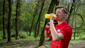 uitdagingen : Young man puts tennis racket on his shoulder and drinks water from plastic bottle to quench thirst. Concept of healthy way of life, sports in park. Prores, Slow Motion, 4k