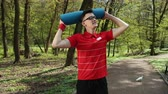 halı : A young man puts a yoga mat on his head and smiles at the camera. Dressed in a red t-shirt. Summer sunny weather in the park. Concept of a healthy way of life and rest. Prores, Slow Motion, 4k Stok Video