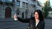 samen bouwen : Beautiful brunette woman looks at her phone and takes selfies in city. Behind good urban architecture. A blogger blog leads live on the phone. Prores, Slow Motion, 4k