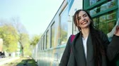 voyage affaire : One beautiful and happy girl standing in front of the train carriage holds a ticket in her hands and says goodbye to her beloved person and relatives before leaving. On her shoulder is a backpack. Vidéos Libres De Droits